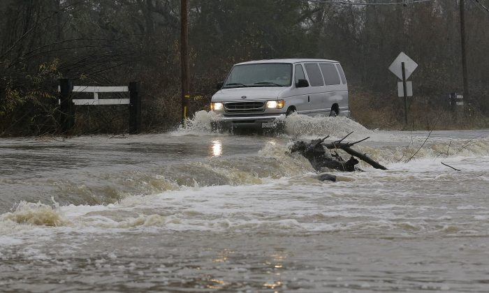 A van drives through flooded water on Green Valley Road in Graton, Calif., on Jan. 7, 2017. (AP Photo/Jeff Chiu)