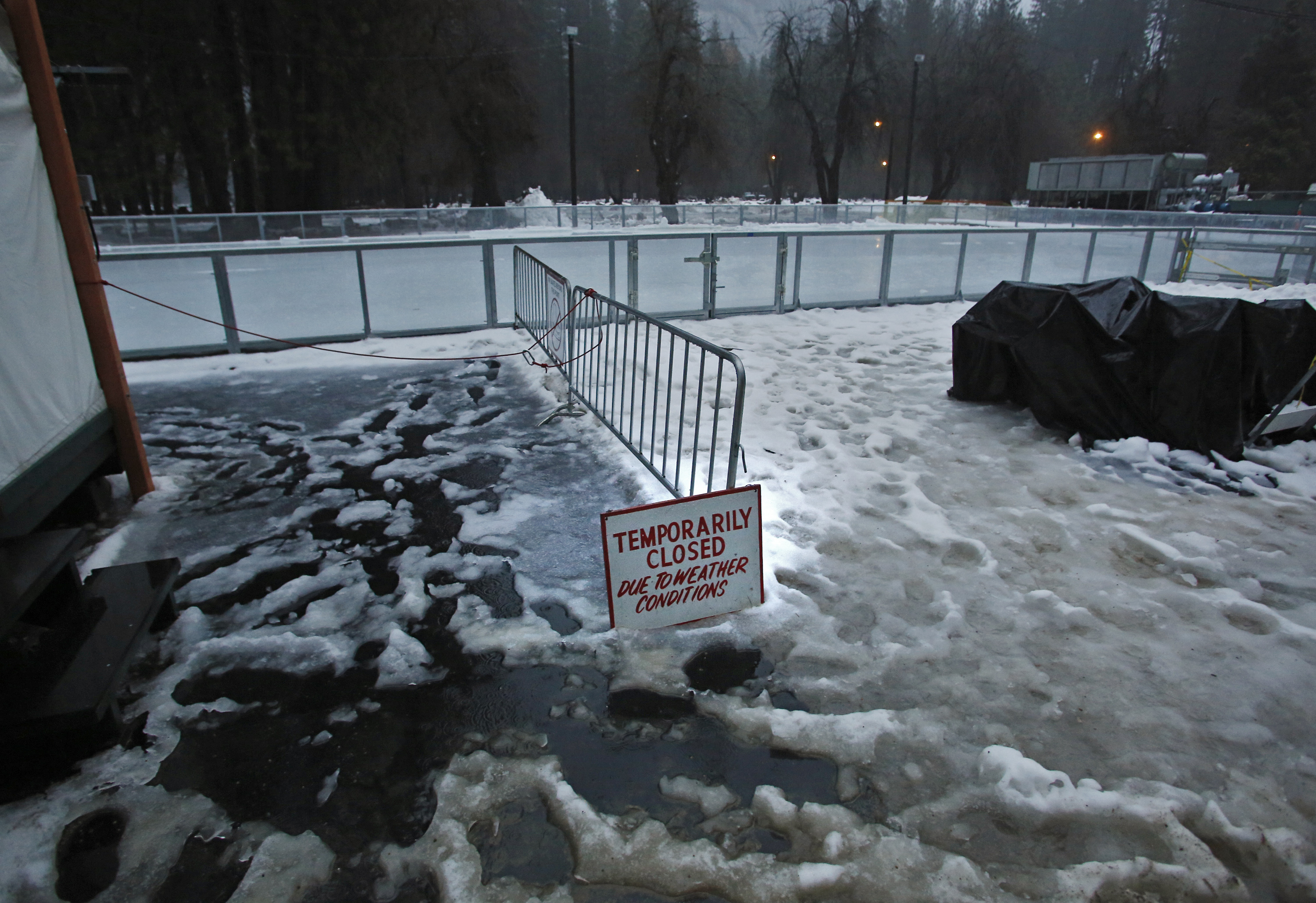 """A """"closed"""" sign stands at the entrance of a normally busy ice rink at the Half Dome Village of Yosemite National Park, Calif., on  Jan 7, 2016. (AP Photo/Gary Kazanjian)"""