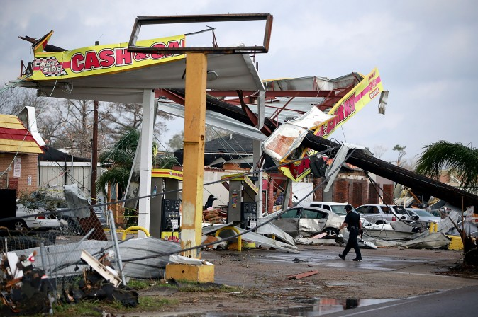 A police officer walks through a damaged gas station along Chef Menture Avenue after a tornado ripped through the eastern part of New Orleans on Feb. 7. According to the weather service, 25 people were injured in the aftermath of the tornado. (Sean Gardner/Getty Images)