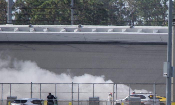Marcel Fässler (white fire suit, helmet) watches the #4 Corvette Racing C7.R burn during Sunday morning's session of the IMSA WeatherTech Roar Before the Rolex 24 at Daytona International Speedway, Jan. 8, 2017.