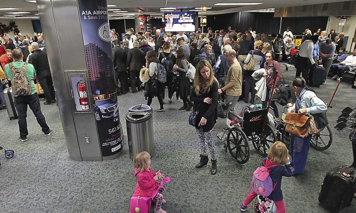 A crowd gathers around the baggage carousel in terminal 2 at Fort Lauderdale-Hollywood International Airport in Fort Lauderdale, Fla., on Jan. 8, 2017. (Patrick Farrell/Miami Herald via AP)