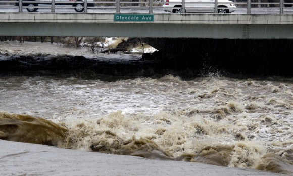 Traffic crosses the raging Truckee River, where it runs near the Grand Sierra hotel-casino along a line that divides the cities of Reno and Sparks, Nev. on Jan. 8, 2017. More than 1,000 homes have been evacuated due to overflowing streams and drainage ditches in the area, which remains under a flood warning through Tuesday. (AP Photo/Scott Sonner)