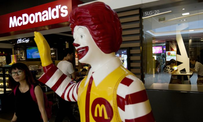 A customer walks past a statue of Ronald McDonald on display outside a McDonald's restaurant in Beijing on July 31, 2014. Fast food giant McDonald's said in a statement Monday, Jan. 9, 2017 it is selling a controlling stake in its China business to a group of investors led by state-owned Chinese conglomerate Citic in a deal worth up to $2.1 billion. (AP Photo/Andy Wong, File)