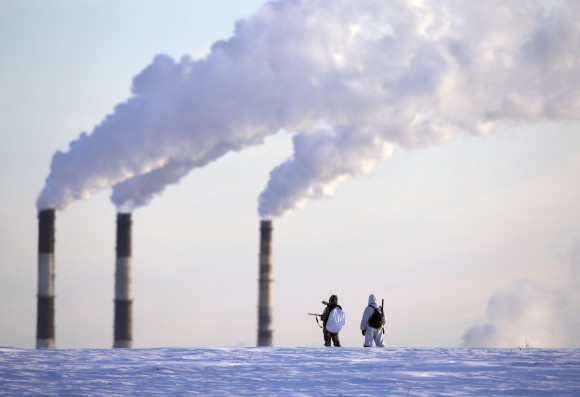 People hunting small animals cross the terrain as smoke is released from a heating plant in morning temperatures of -19 degrees Celsius (-2.2 degrees Fahrenheit) in Minsk, Belarus, Monday, Jan. 9, 2017. (AP Photo/Sergei Grits)