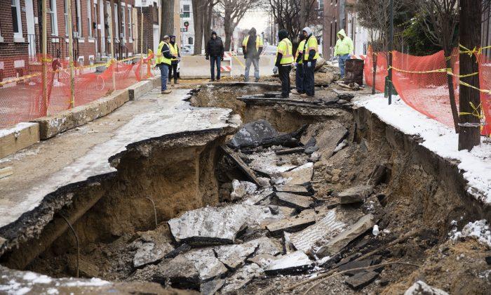 Workers inspect a sinkhole in Philadelphia on Jan. 9, 2017. (AP Photo/Matt Rourke)