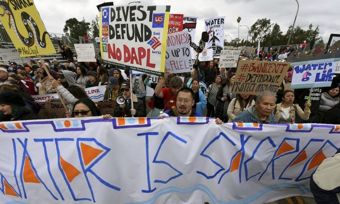 Protesters rally against the Dakota Access Pipeline behind the 128th Rose Parade in Pasadena, Calif., on Jan. 2, 2017. (AP Photo/Michael Owen Baker)