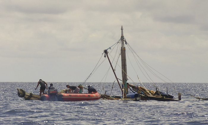 Members of the Philippine Coast Guard, left, approach the almost sunken fishing boat of Filipino fishermen who were killed by suspected pirates in waters near Zamboanga City, southern Philippines Tuesday, on Jan. 10, 2017. (Philippine Coast Guard via AP)