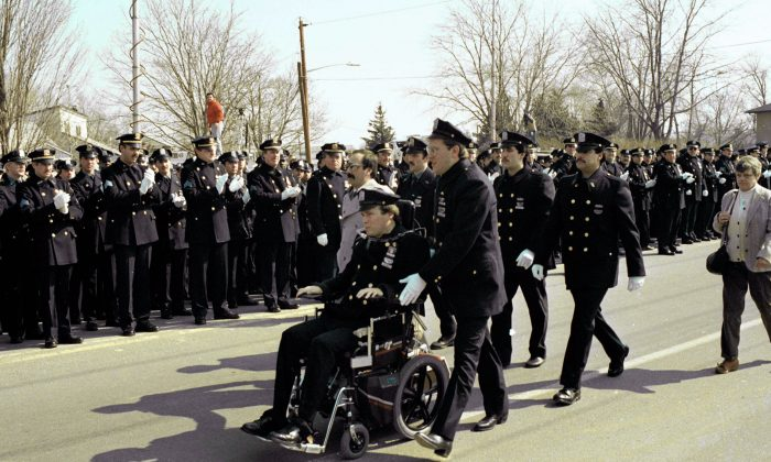 Paralyzed police officer Steven McDonald receives applause from members of the New York City Police Department as he arrives for funeral services at Seaford, N.Y., for slain officer Edward Byrne, in this file photo. (AP Photo/David Bookstaver)