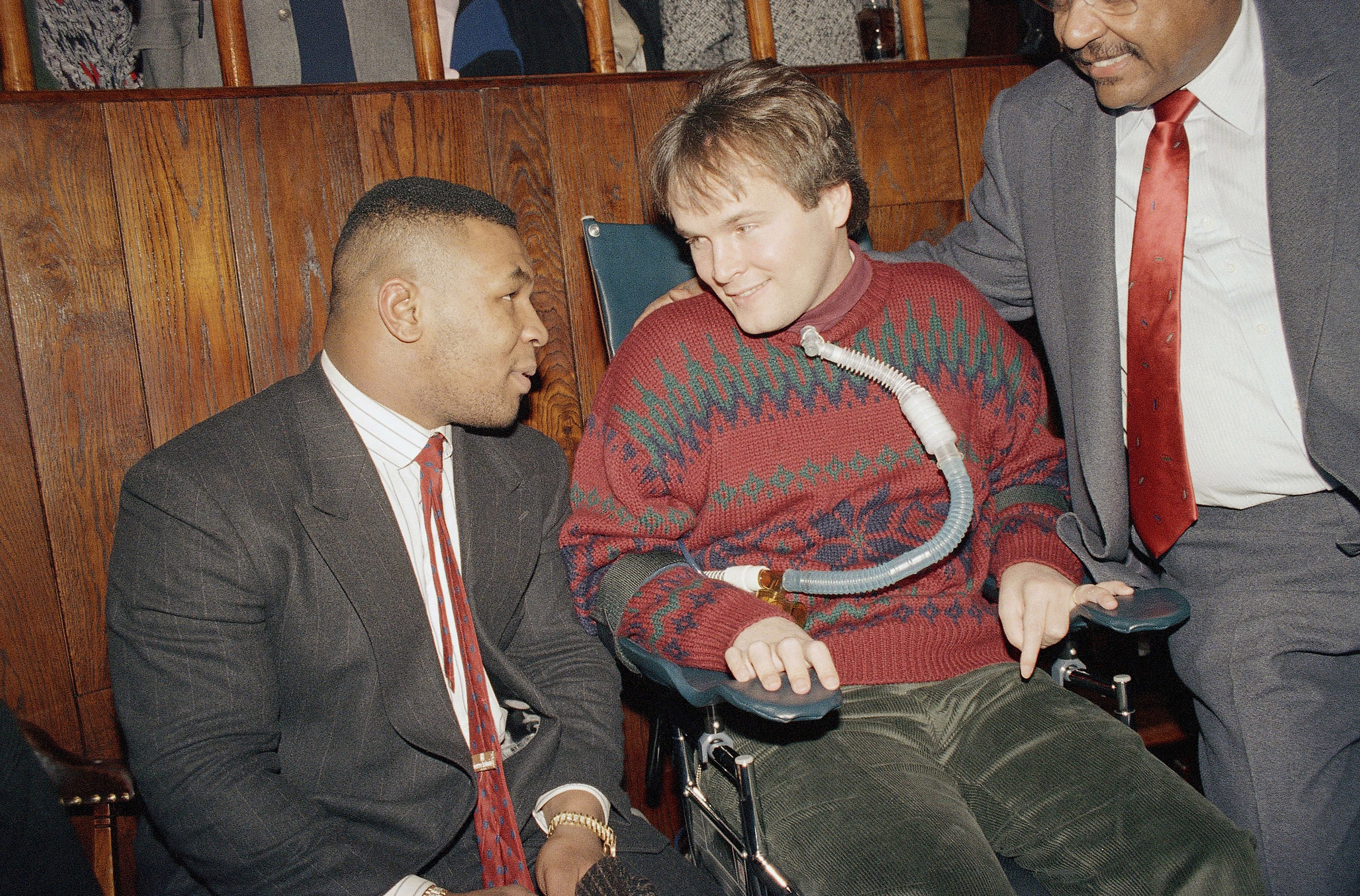 Mike Tyson (R) meets with paralyzed police officer Steven McDonald at the Patrolmen's Benevolent Association Christmas party held at Jimmy Weston's restaurant in New York. (AP Photo/Gerald Herbert)