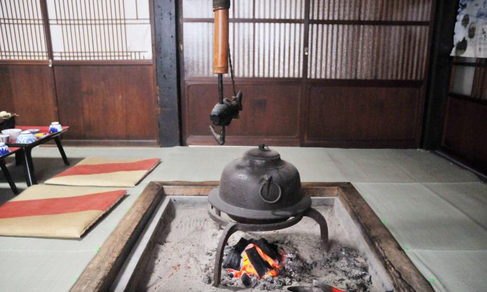 Figure 2 An irori with a jizaikagi (自在鉤), which is a hook consisting of an iron rod within a bamboo tube, and a fish-shaped yokogi (橫木). (Sun Mingguo/Epoch Times)