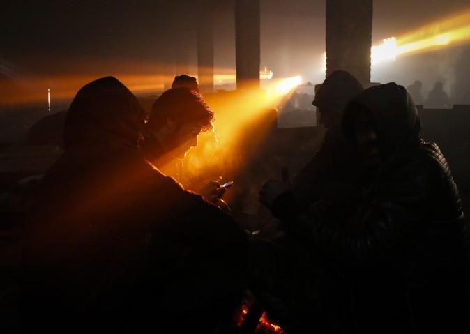 Migrants warm themselves by a fire inside a derelict customs warehouse on in Belgrade, Serbia, on Jan. 8. (Srdjan Stevanovic/Getty Images)