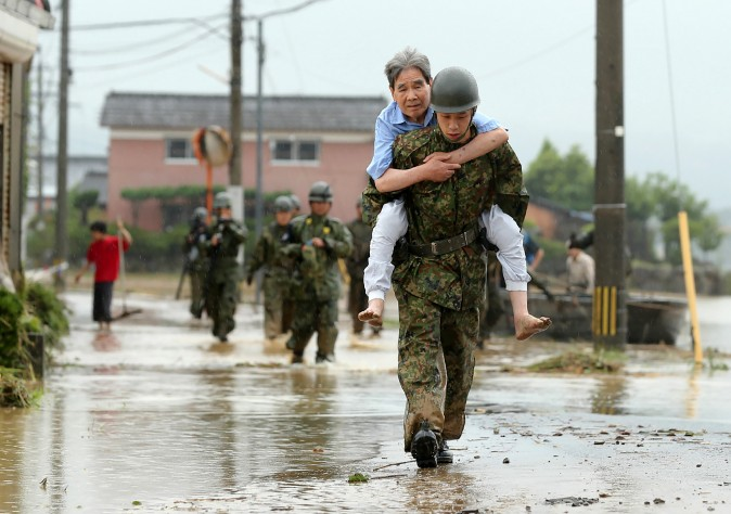 apanese soldiers help local residents evacuate from flooded area in Asakura, Fukuoka prefecture, on July 6, 2017. At least 15 people are missing after huge floods swept away houses in southern Japan, tearing up roads as roiling waters surged through villages, authorities said, after unprecedented rainfall. (STR/AFP/Getty Images)