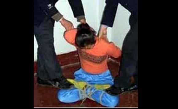 Torture reenactment: Tied with legs crossed (Minghui.org)
