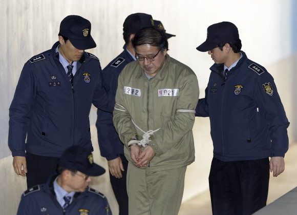 Ahn Jong-beom, second from right, disgraced South Korean President Park Geun-hye's former senior secretary for policy coordination, arrives for his trial at the Seoul Central District Court in Seoul, South Korea, on Jan. 11, 2017. (AP Photo/Ahn Young-joon)