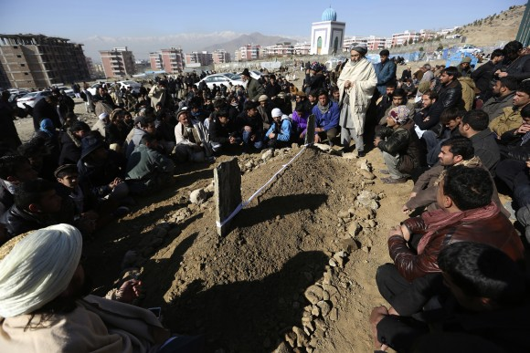 Villagers pray in front of the grave of a victim of Tuesday's two bombings in Kabul, Afghanistan, Wednesday, Jan. 11, 2017. The Taliban claimed attacks earlier on Tuesday in Kabul that killed at least 38 people and wounded dozens. (AP Photo/Rahmat Gul)