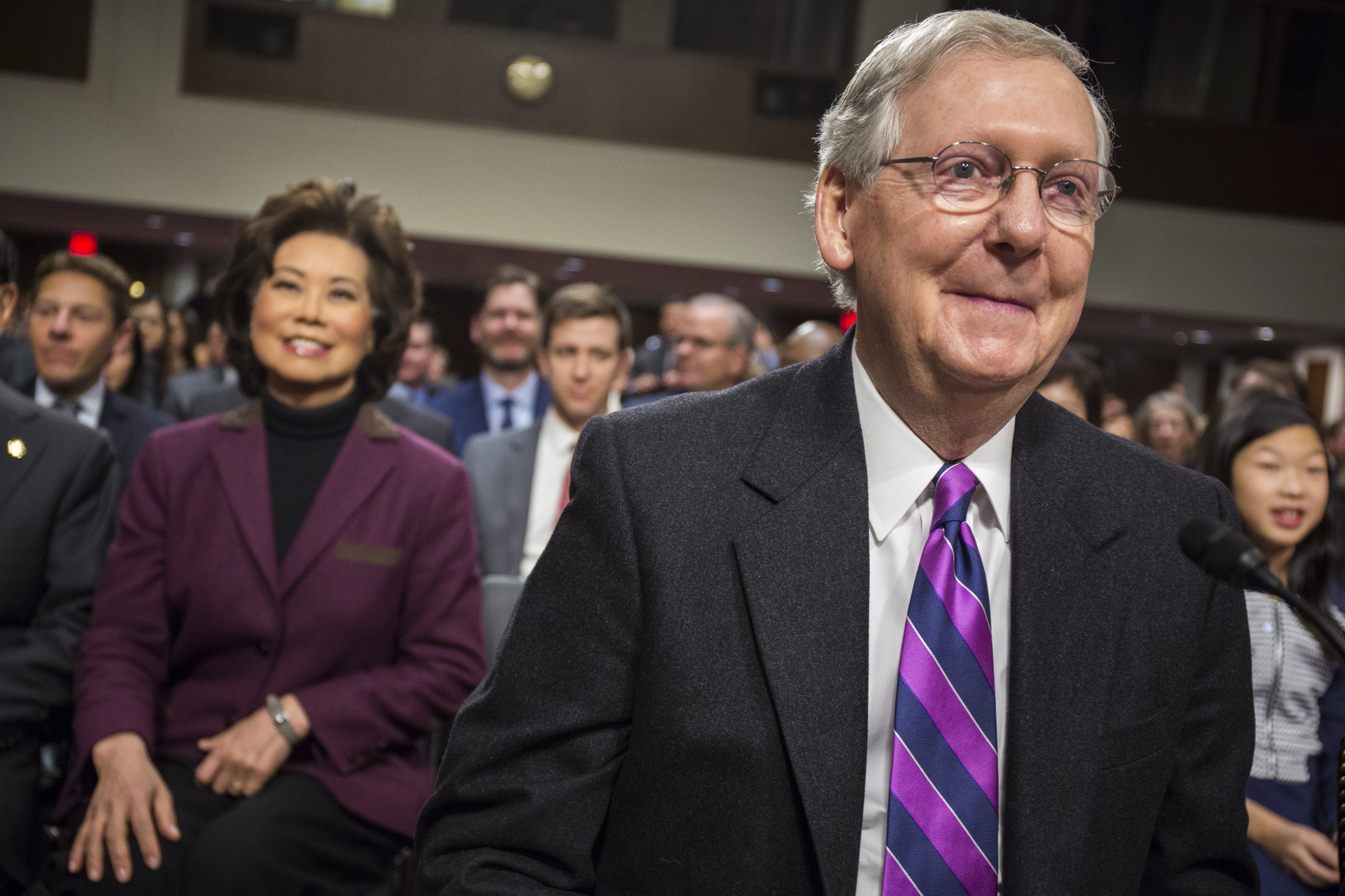 Transportation Secretary-designate Elaine Chao watches as her husband, Senate Majority Leader Mitch McConnell of Ky., arrives on Capitol Hill in Washington on Jan. 11, 2017. (AP Photo/Zach Gibson)