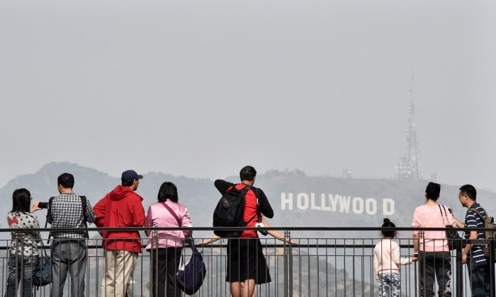 Tourists watch and photograph the Hollywood sign from a shopping mall terrace in Los Angeles, Calif. on Feb. 20, 2015. (MLADEN ANTONOV/AFP/Getty Images)
