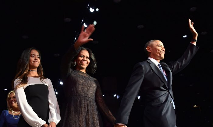 US First Lady Michelle Obama (C) and US President Barack Obama wave to supporters as daughter Malia looks on after the President delivered his farewell address in Chicago, Illinois on Jan. 10, 2017. Barack Obama closes the book on his presidency, with a farewell speech in Chicago. (NICHOLAS KAMM/AFP/Getty Images)