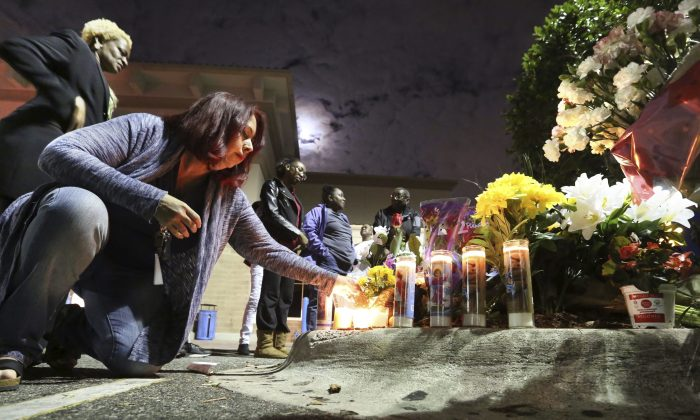 Tricia Dennis and Orlando city commissioner Regina Hill, far left, pay their respects at a makeshift memorial to honor an Orlando police sergeant killed Monday at the parking lot of a Wal-Mart store and an Orange County Sheriff's Office deputy before a candlelight vigil at the store in Orlando, Fla., on Jan. 10, 2017. (Joe Burbank/Orlando Sentinel via AP)