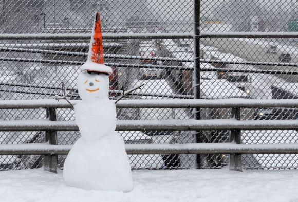 A snowman wearing a traffic cone hat is shown on an overpass as early morning traffic is at a standstill in the background on Interstate 5 headed into Portland, Ore., on  Jan. 11, 2017. (AP Photo/Don Ryan)