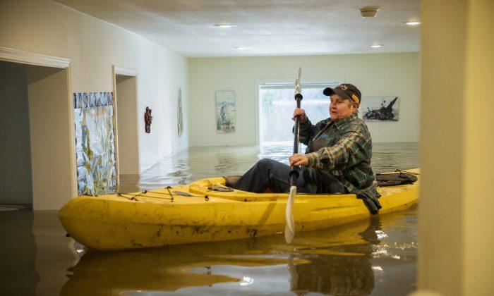 Lorin Doeleman uses a kayak to check her flooded home in Guerneville, Calif., on Jan. 11, 2017. (Santiago Mejia/San Francisco Chronicle via AP)