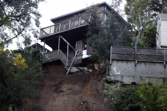 A home sits on the edge of a hill after a slab of concrete slid down a rain-soaked hillside in Los Angeles' Hollywood Hills neighborhood, on Jan. 11, 2017. (AP Photo/Damian Dovarganes)