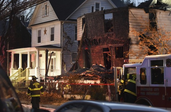 Baltimore City firefighters remain on the scene early Thursday, Jan. 12, 2017, after a fire on Springwood Avenue in northeast Baltimore. Several children and an adult were taken to an area hospital. Six children are still missing. (Jerry Jackson/The Baltimore Sun via AP)