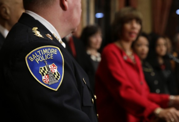 The Baltimore Police Department seal is seen on Commissioner Kevin Davis' uniform as he listens to Baltimore Mayor Catherine Pugh during a joint news conference in Baltimore, Thursday, Jan. 12, 2017, to announce the Department's commitment to a sweeping overhaul of its practices under a court-enforceable agreement with the federal government. (AP Photo/Patrick Semansky)