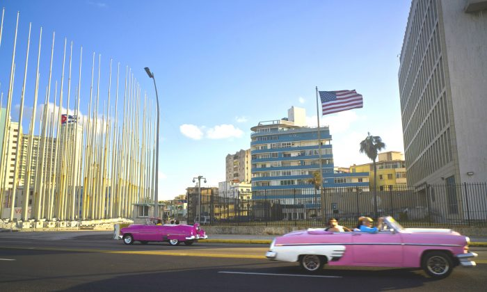 Tourists ride in classic American convertible cars past the United States embassy (R) in Havana, Cuba on Jan. 12, 2017. (AP Photo/Ramon Espinosa)