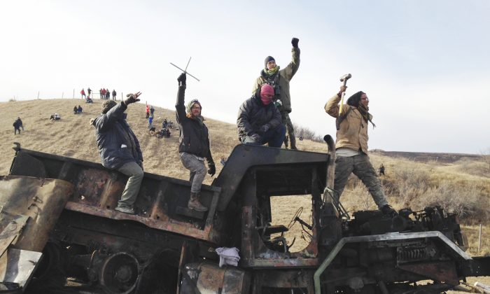 Protesters against the Dakota Access oil pipeline stand on a burned-out truck near Cannon Ball, N.D., that they removed from a long-closed bridge a day earlier on a state highway near their camp, in this file photo. (AP Photo/James MacPherson, File)