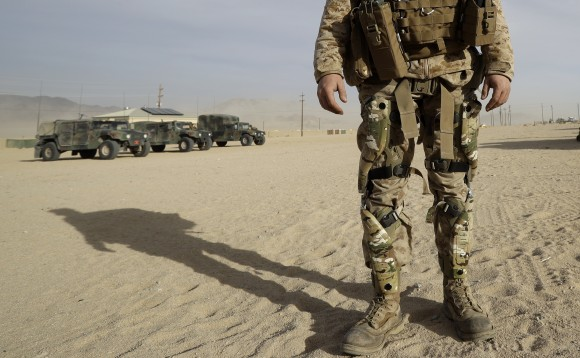 A Marine wears knee braces and a backpack that harvest energy from his movements during an exhibition of green energy technology in Twentynine Palms, Calif. on Dec. 7, 2016. (AP Photo/Gregory Bull)