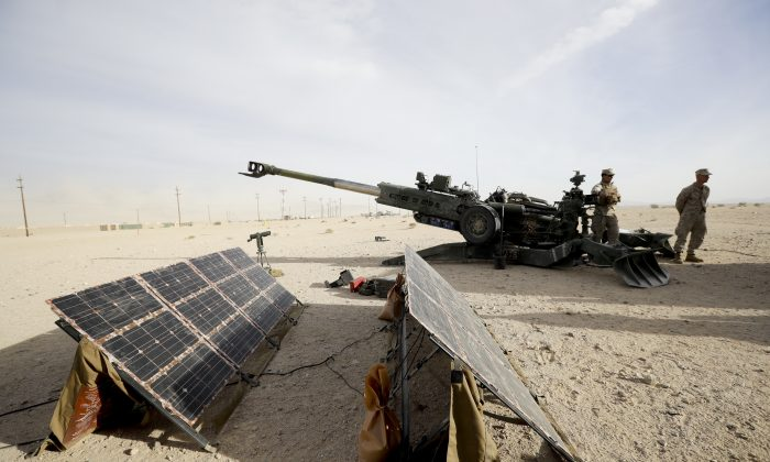 Marines stand near an artillery piece that links to solar panels during an exhibition of green energy technology in Twentynine Palms, Calif. on Dec. 7, 2016. (AP Photo/Gregory Bull)