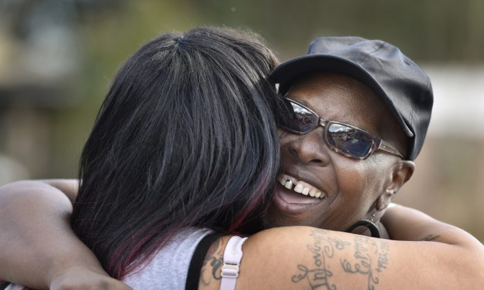 Velma Aiken, the paternal grandmother of Kamiyah Mobley, who was kidnapped as an infant 18 years ago, gets a congratulatory hug from a family member after Mobley was found safe in Jacksonville, Fla, on Friday, Jan. 13, 2017.  (Will Dickey /The Florida Times-Union via AP)