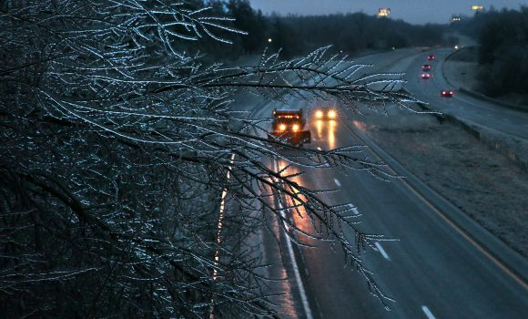 A Missouri Department of Transportation salt truck spreads ice melt on Interstate 55 as coated tree branches sway overhead as seen from the Main Street bridge in Festus, Mo., on Jan. 13, 2017. (Robert Cohen/St. Louis Post-Dispatch via AP)