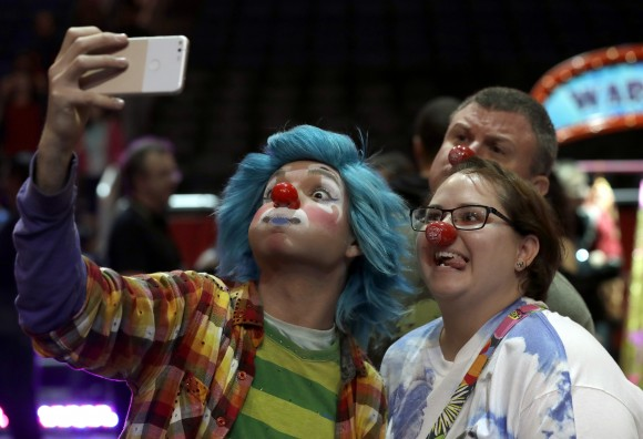 A Ringling Bros. and Barnum & Bailey clown takes a selfie with Jennifer and Kevin Fox, of Fort Pierce, Fla., on Jan. 14, 2017. (AP Photo/Chris O'Meara)