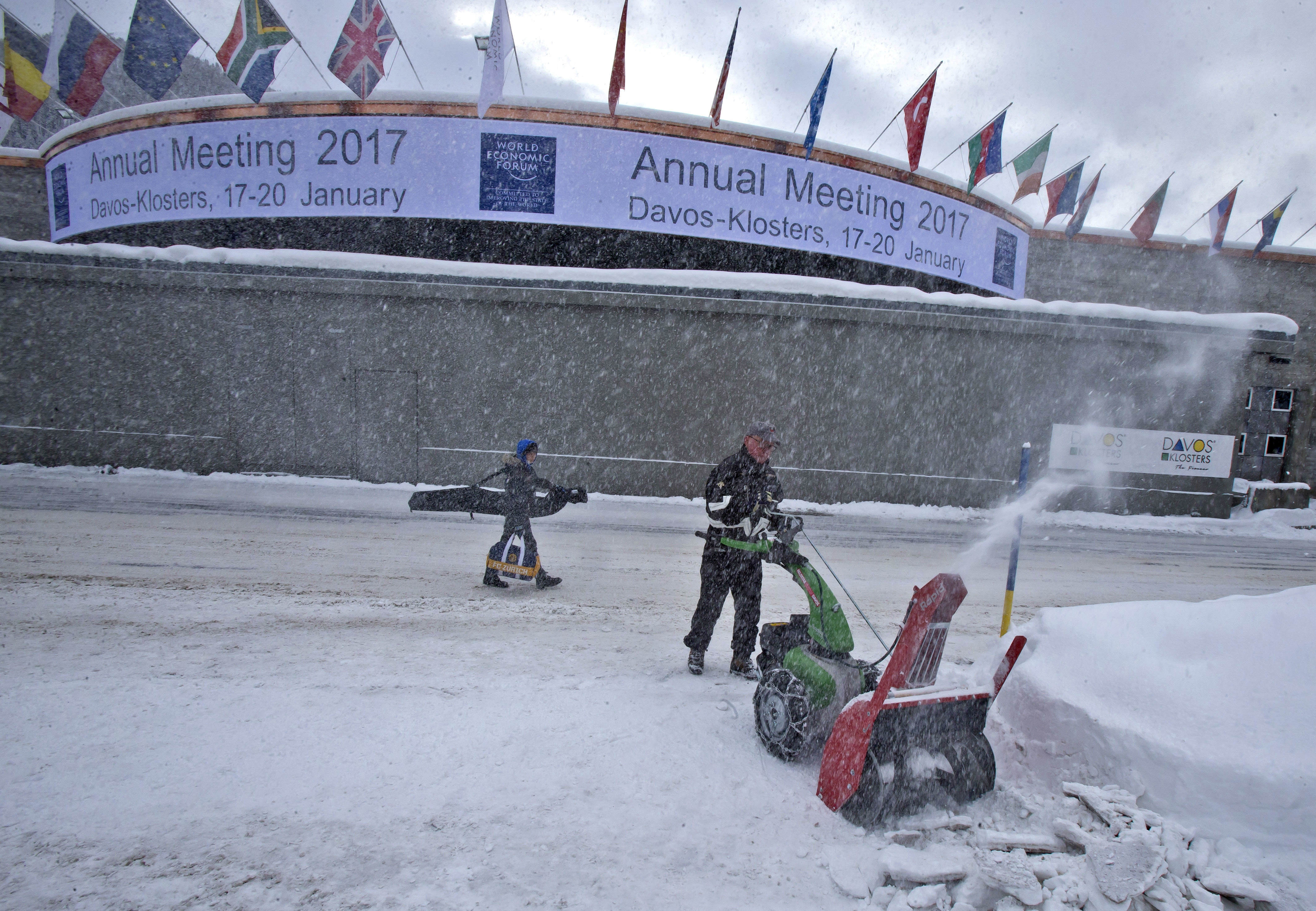 A municipality worker uses a snow blower to clear the area in front of the congress center where the annual meeting, World Economic Forum, will take place in Davos, Switzerland on Jan. 15, 2017. (AP Photo/Michel Euler)