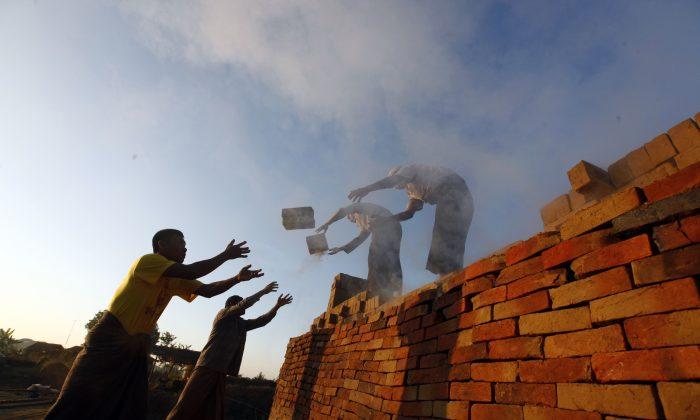 Workers unload bricks at a brick-making factory in Naypyitaw, Myanmar, on Jan. 13, 2017. (AP Photo/Aung Shine Oo)