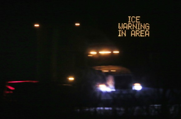 Traffic moves past an icing warning sign at night on I-70 west Lawrence, Kan., on Jan. 14, 2017. (AP Photo/Orlin Wagner)