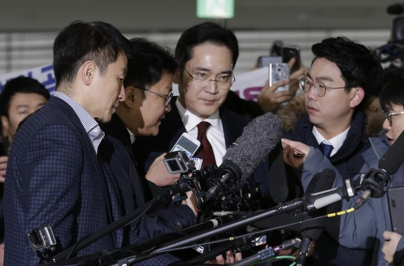 In this fie photo, Lee Jae-yong, center, vice chairman of Samsung Electronics, arrives to be questioned as a suspect in bribery case in the massive influence-peddling scandal that led to the president's impeachment at the office of the independent counsel in Seoul, South Korea. (AP Photo/Ahn Young-joon, Pool)
