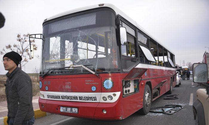 A bus is damaged by a roadside bomb in the predominantly Kurdish city of Diyarbakir, in southeastern Turkey, Monday Jan. 16, 2017. The bomb killed more than three policemen and wounded two others, according to the state-run news agency. Turkey's southeast has witnessed renewed conflict between state security forces and Kurdish militants that has left thousands dead in the last year. (Canan Altintas/DHA-Depo Photos via AP)