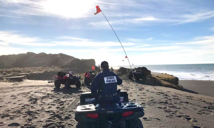 OSP troopers on all-terrain vehicles search a beach about two miles north of Cape Blanco, Oregon, where a father and his young son were swept out to sea Sunday as they walked near the surf. (Oregon State Police via AP)