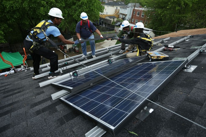 Workers install solar panels on a home in Washington on May 3, 2016. (Alex Wong/Getty Images)