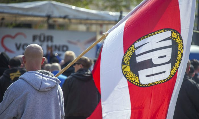 A man with a flag with National Democratic Party, NPD,  logo attends a  rally of the NPD in Schwerin, Germany, on May 1, 2016. (Jens Buettner/dpa via AP, file)
