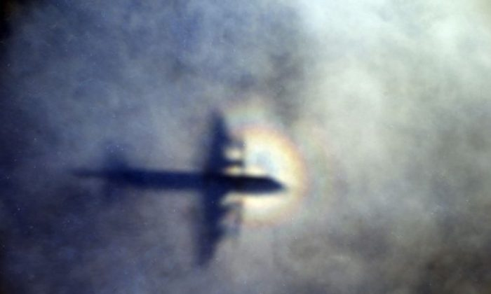 In this March 31, 2014 file photo, the shadow of a Royal New Zealand Air Force P3 Orion is seen on low level cloud while the aircraft searches for missing Malaysia Airlines Flight MH370 in the southern Indian Ocean, near the coast of Western Australia. After nearly three years, the hunt for Malaysia Airlines Flight 370 ended in futility and frustration on Tuesday, Jan. 17, 2017, as crews completed their deep-sea search of a desolate stretch of the Indian Ocean without finding a single trace of the plane. (AP Photo/Rob Griffith, File)