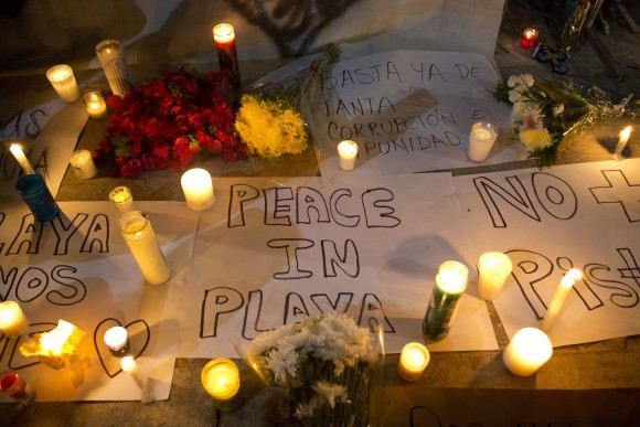 """Candles sit atop banners proclaiming in Spanish """"Peace in Playa,"""" """"No more pistols,"""" and """"Enough already of so much corruption and impunity,"""" outside the Blue Parrot club, where several people were killed in early morning gunfire, in Playa del Carmen, Mexico, on Jan. 16, 2017. (AP Photo/Rebecca Blackwell)"""