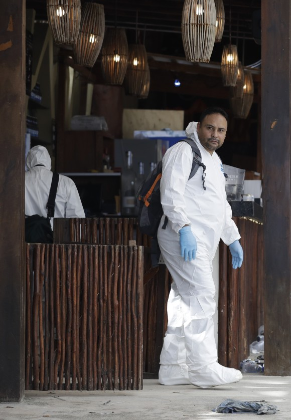 A forensic investigator walks inside the Blue Parrot club, one day after a deadly early morning shooting in Playa del Carmen, on Tuesday, Jan. 17, 2017. (AP Photo/Rebecca Blackwell)
