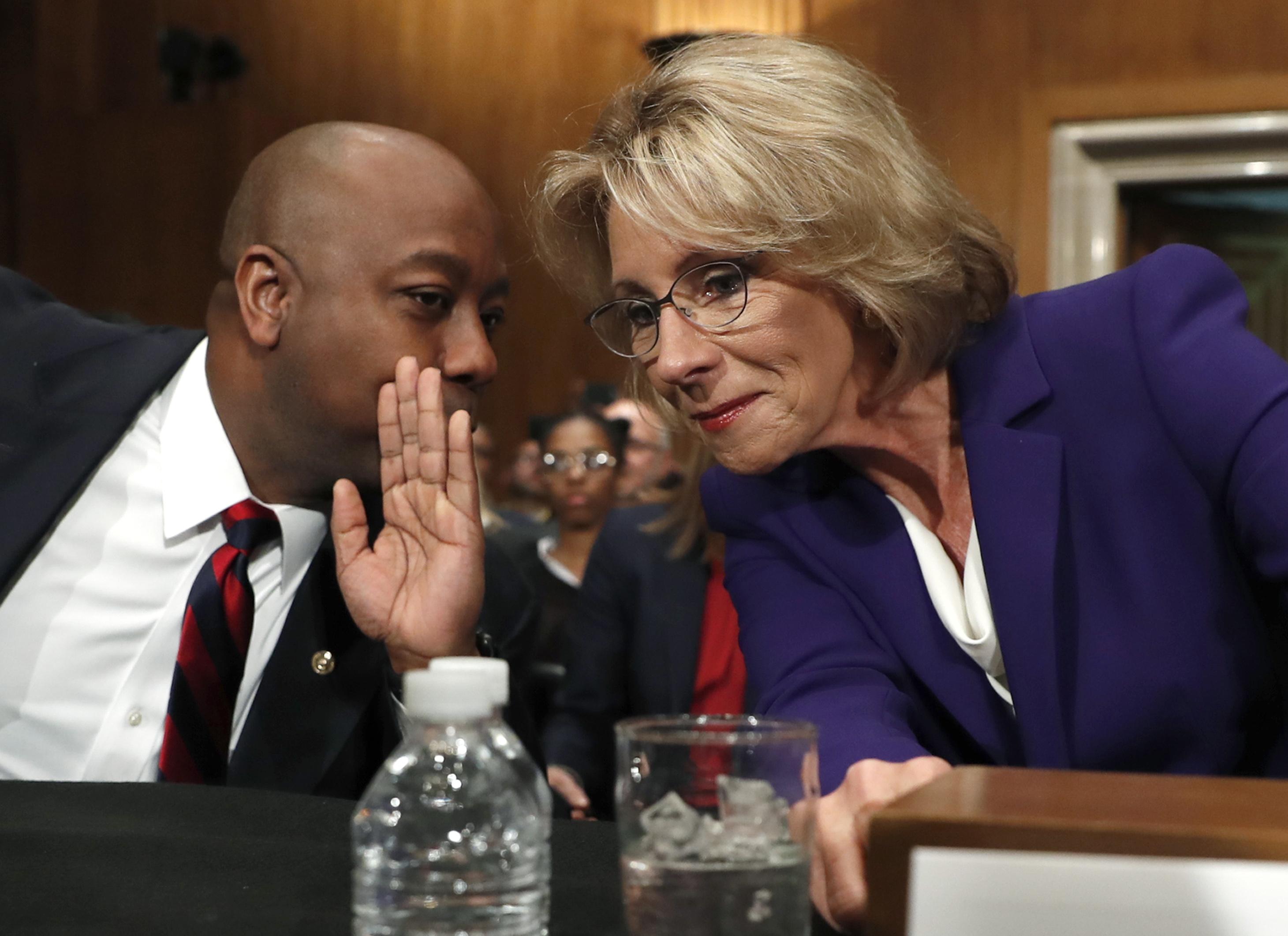 Education Secretary-designate Betsy DeVos talks to Sen. Tim Scott, R-S.C., before testifying on Capitol Hill in Washington on Jan. 17, 2017. (AP Photo/Carolyn Kaster)