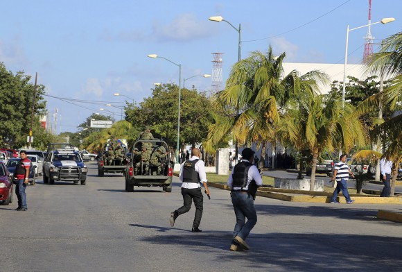 Police run near the state prosecutors' office after a gunmen opened fire on the building in Cancun, Mexico, on Jan. 17, 2017. (AP Photo)
