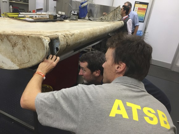 FILE - In this July. 20, 2016, file photo released by the Australian Transport Safety Bureau (ATSB), staff examine a piece of aircraft debris at their laboratory in Canberra, Australia. The flap was found in June 2016 by residents on Pemba Island off the coast of Tanzania and officials had previously said it was highly likely to have come from flight MH370. While search crews spent years trawling in futility through a remote patch of the Indian Ocean for the missing Malaysia Airlines Flight 370, people wandering along beaches on the other side of the ocean began spotting debris that washed ashore. Those pieces provided key information and raised questions whether Malaysia, Australia and China - who funded the hunt for the underwater wreckage - missed key opportunities by failing to organize coastal searches for plane parts. (ATSB via AP, File)