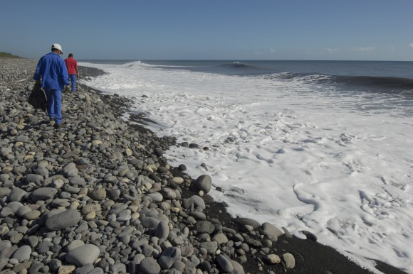 In this file photo, municipal workers search Reunion Island beaches where expected debris of the missing Malaysia Airlines Flight 370 could be washed up onto the shore near Saint-Andre, on the French Island of Reunion. (AP Photo/Fabrice Wislez)